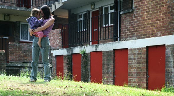 Lady Standing Outside Flats Holding Baby